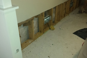 Cut sheetrock shows preparation to install french drain on finished wall | Before